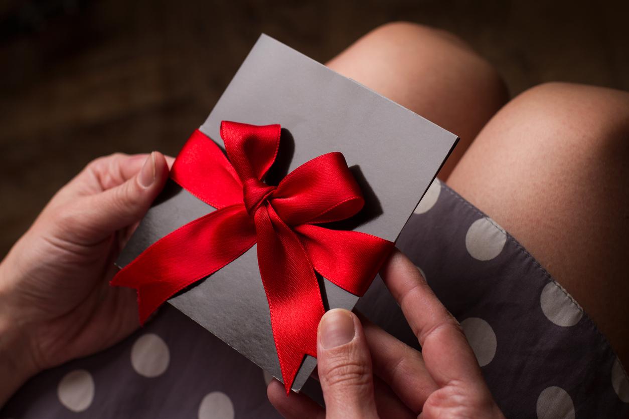 cartes de voeux et ruban rouge dans les mains d'une femme